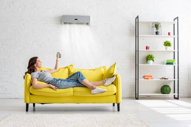 atractiva joven acostada en el sofá amarillo bajo el aire acondicionado en casa - foto de stock