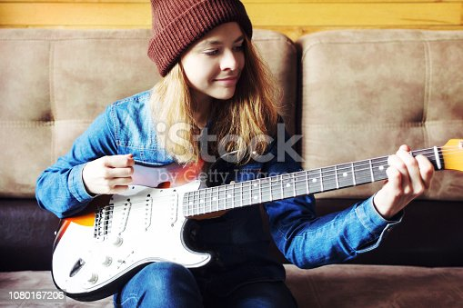 Teenager playing guitar at home.