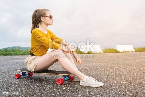 Attractive young girl with a tattoo on her arm in sunglasses and shorts sits on her longboard in a suburban parking on a background of gray sky. Millennials generation and leisure concept.