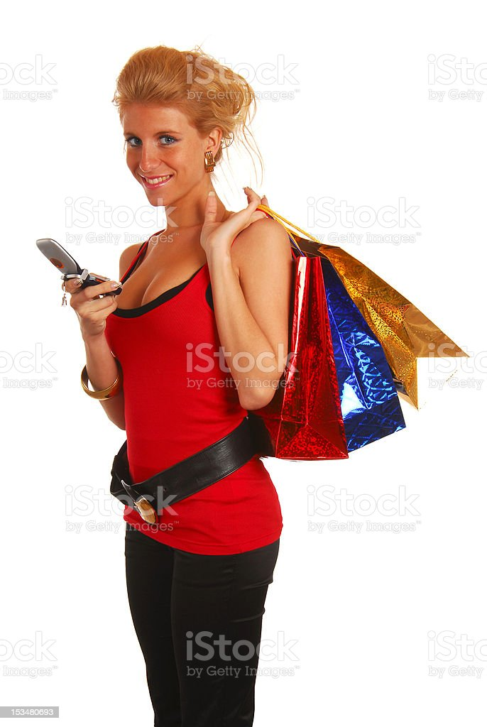 Attractive young girl with shopping bags and mobile phone royalty-free stock photo