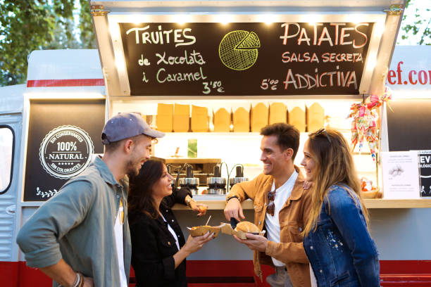 Attractive young group of friends visiting and buying fast food in eat market in the street. Shot of attractive young group of friends visiting and buying fast food in eat market in the street. food truck stock pictures, royalty-free photos & images