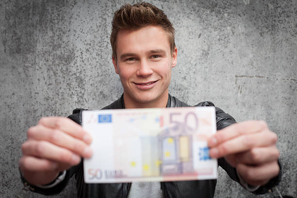Attraktive junge Mann hält Fünfzig euro note – Foto