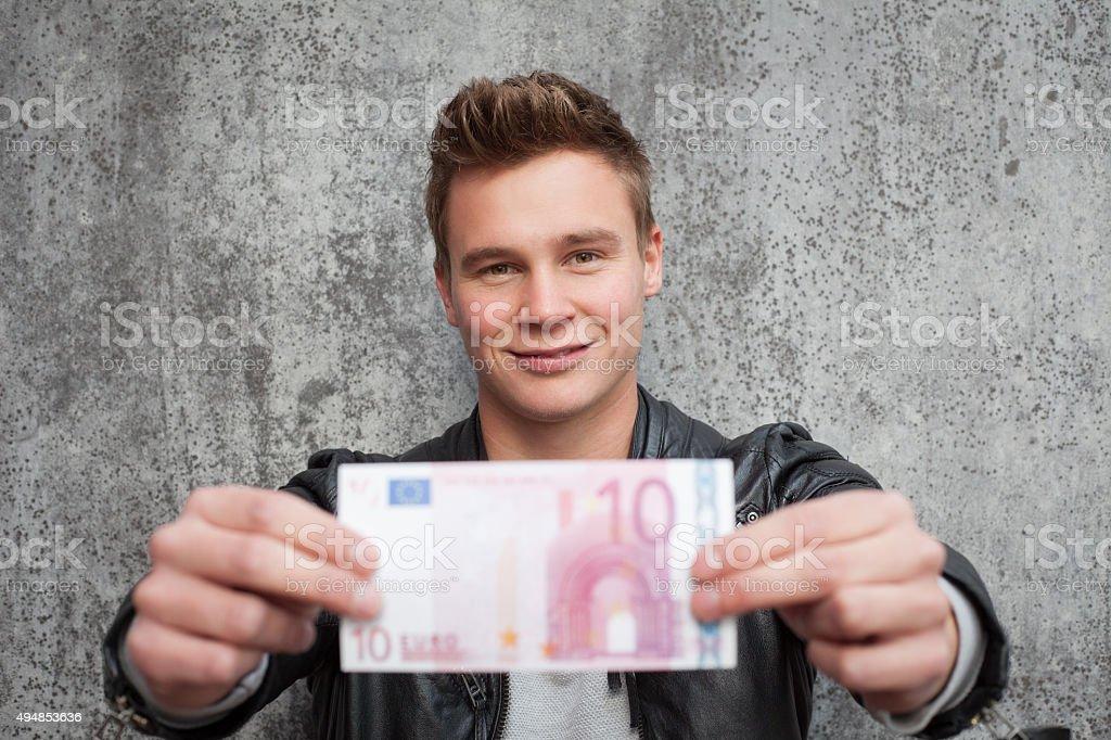 Attraktive junge Mann hält zehn euro note – Foto