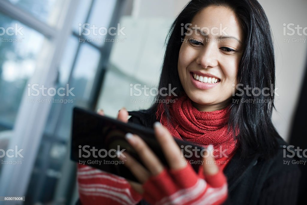 Attractive, young, happy Asian woman using smart phone or phablet. stock photo