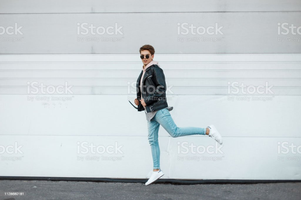Attractive young hipster man in black glasses in a fashionable...