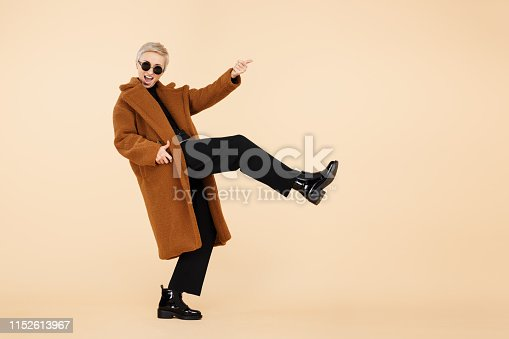 Attractive young hipster woman with blonde short hair wearing a coat and sunglasses play on invisible guitar isolated over beige background. Full lengh photo