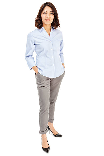Attractive Young Hispanic Businesswoman Photo of an attractive young Hispanic businesswoman in blue button-down shirt, standing with hands in pockets; isolated on white. hands in pockets stock pictures, royalty-free photos & images