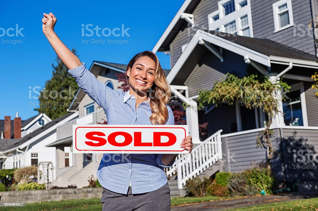 Attractive Young Hispanic Realtor with SOLD Sign stock photo