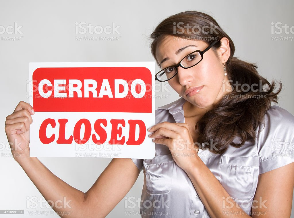Attractive young Hispanic woman holds up 'Cerrado - Closed' sign royalty-free stock photo