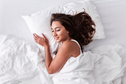 Photo of a young Hispanic woman lying in bed, on her side, happily asleep with a smile on her face.Photo of an attractive young hispanic woman sleeping blissfully.