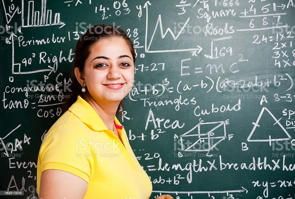 Attractive Young Indian Mathematics Teacher in a Classroom with Greenboard stock photo