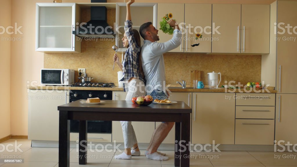 Attractive young joyful couple have fun dancing and singing while cooking in the kitchen at home stock photo