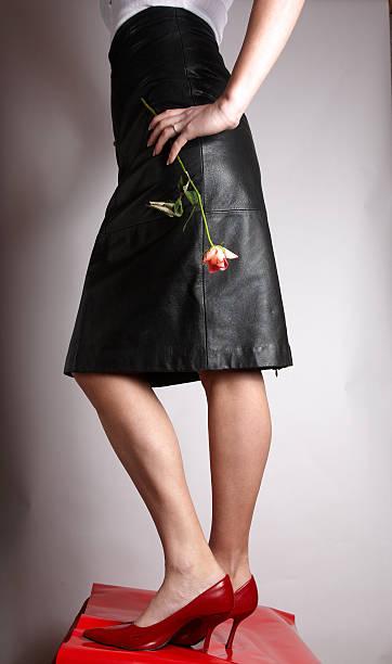 attraktive junge frau in schwarzem leder minirock - rote bleistiftröcke stock-fotos und bilder