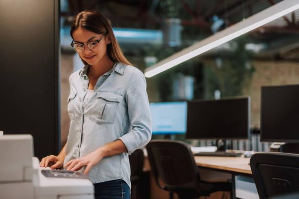 aantrekkelijke jonge dame in glazen werken bij moderne kantoor - kopiëren stockfoto's en -beelden