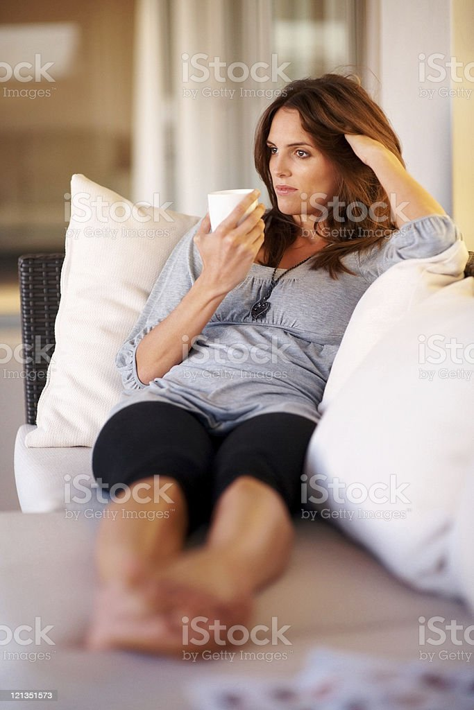 Attractive, young lady relaxing on sofa with cup of coffee royalty-free stock photo