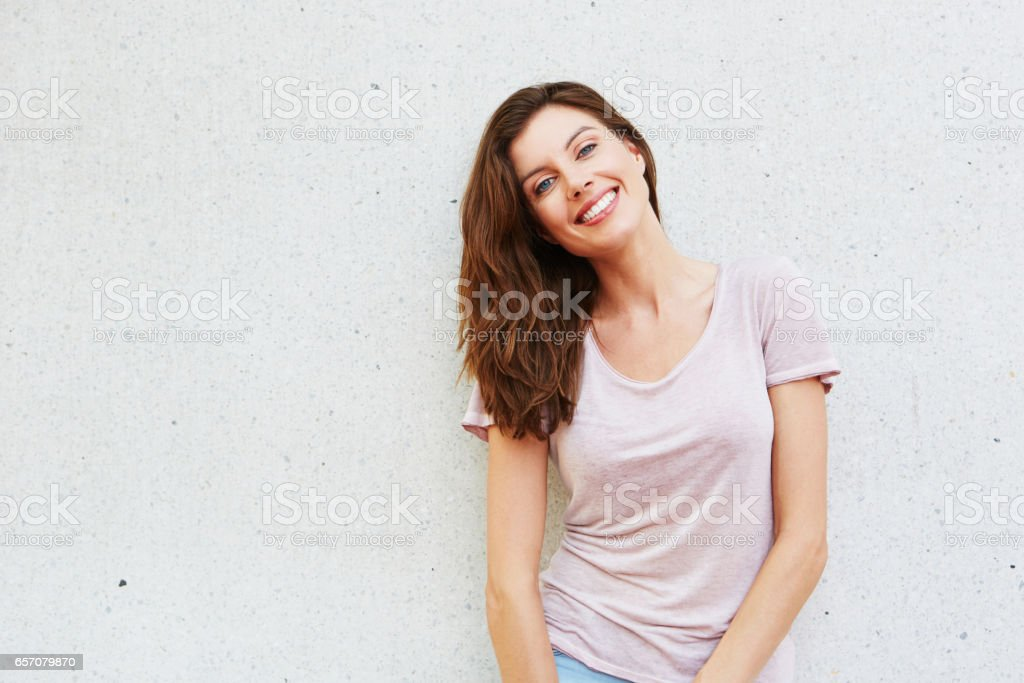 attractive young lady smiling against white background stock photo