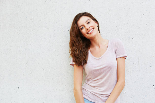 aantrekkelijke jonge dame glimlachend tegen witte achtergrond - mid volwassen vrouw stockfoto's en -beelden