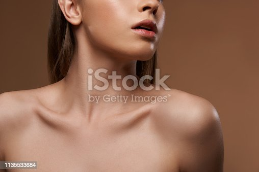 Cropped close up portrait of charming girl with perfect silky skin keeping mouth slightly open and demonstrating her long graceful neck