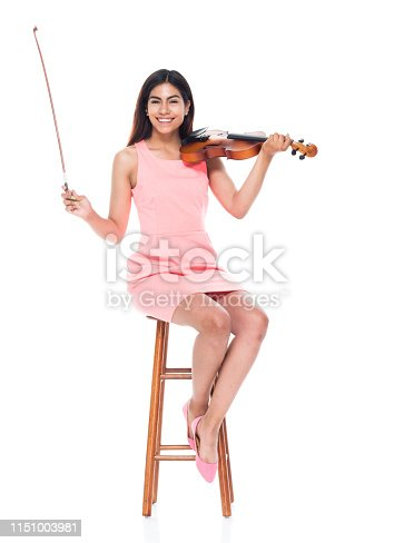 Attractive young latino female playing the violin while sitting on stool