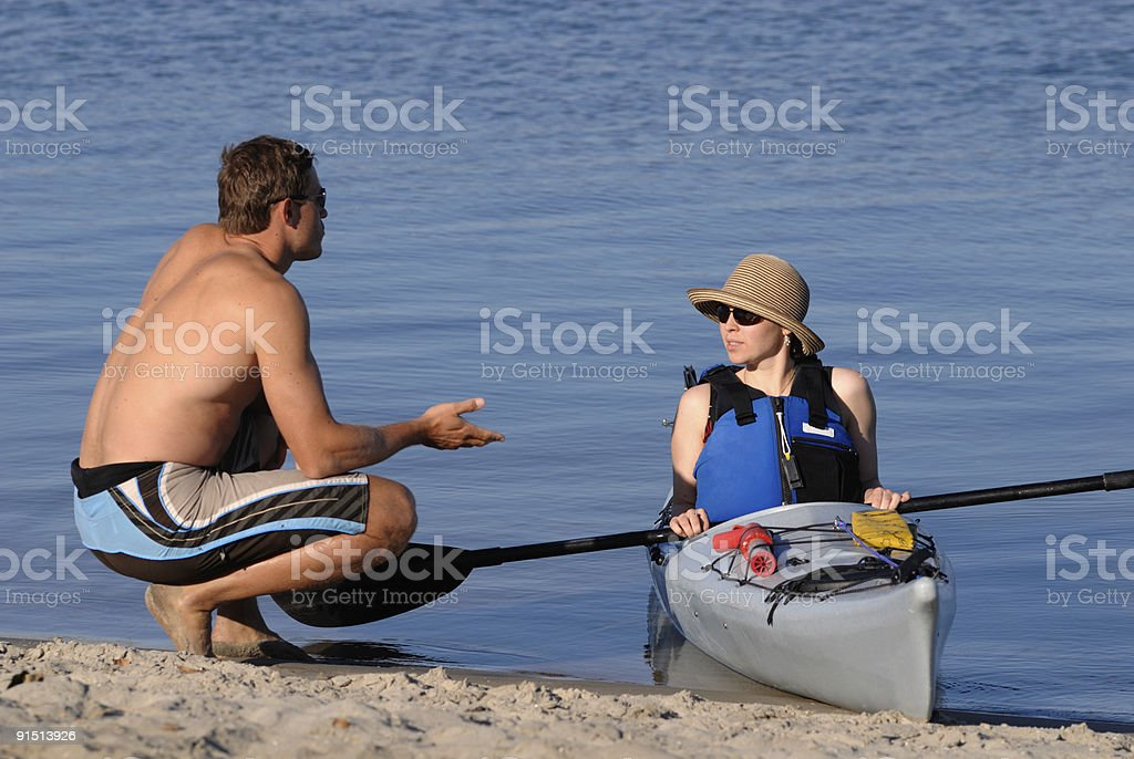 Attractive young man and woman talking on a beach royalty-free stock photo