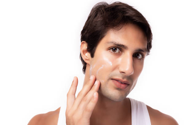 Attractive young man apply moisturizer, cream face or sunscreen on beauty face for nourishing face skin, protecting from sunlight Cool guy has nice facial skin because he look after himself well stock photo