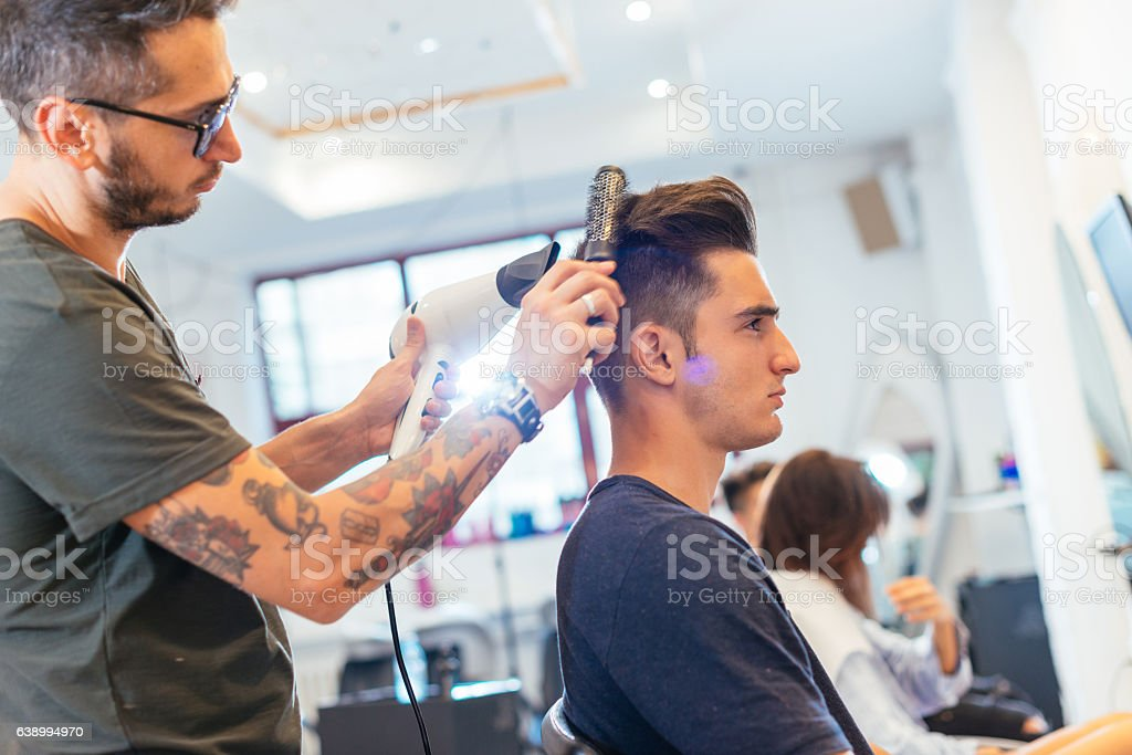 Attractive young man at hair stylist stock photo