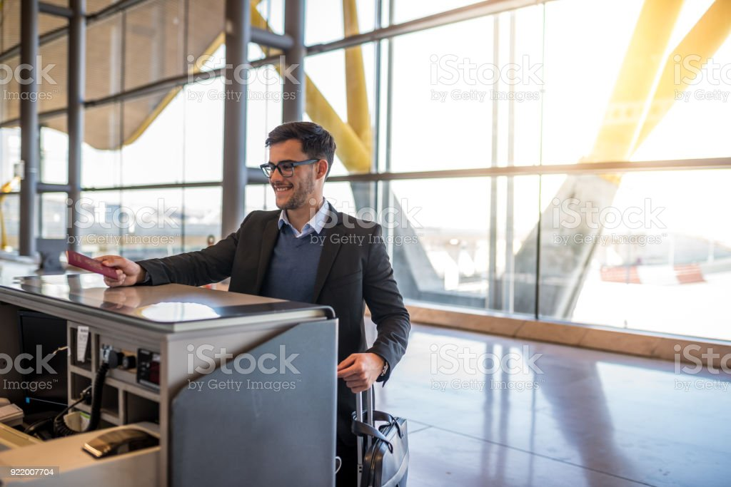 attractive young man check-in at the airport with his passport stock photo