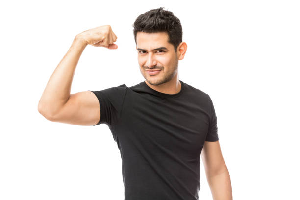 Attractive Young Man Dressed In Black Tshirt Showing His Biceps Attractive young man dressed in black tshirt showing his biceps over white background flexing muscles stock pictures, royalty-free photos & images