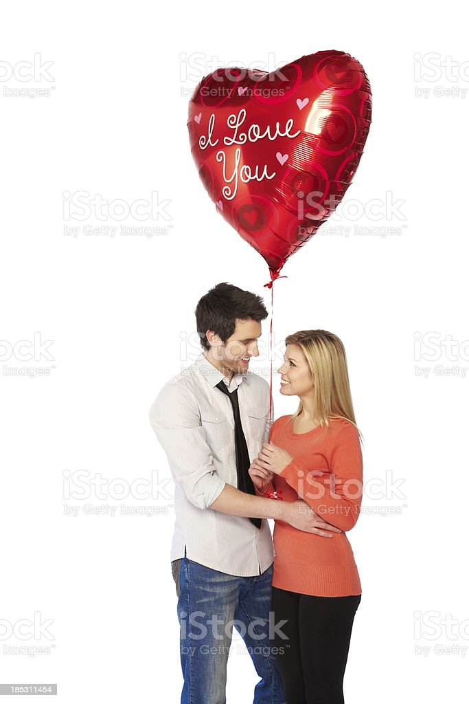 Attractive young man gifting red heart shaped balloon stock photo