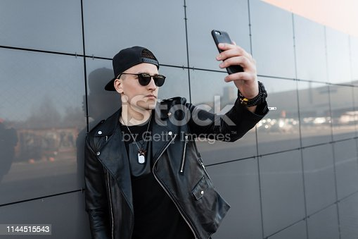 Attractive young man hipster in a stylish leather jacket in a black baseball cap in a t-shirt makes a selfie standing near a gray modern mirror building in the city. Fashionable urban guy for a walk.