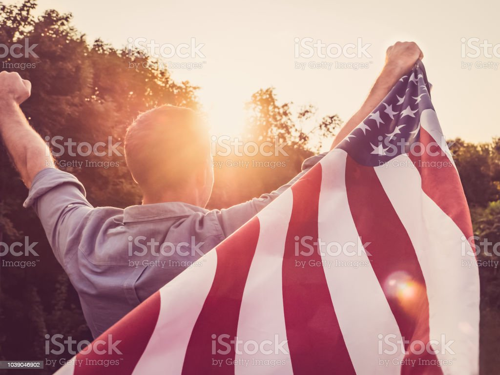 Attractive, young man holding a US flag stock photo