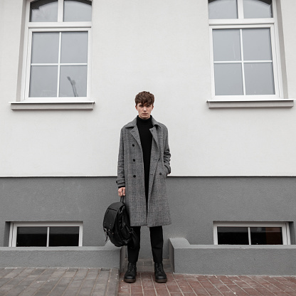 627398448 istock photo Attractive young man in a long plaid fashionable coat in black stylish boots with a cool leather backpack stands on the street near a white building. Handsome european guy outdoors. Youth menswear. 1199258706
