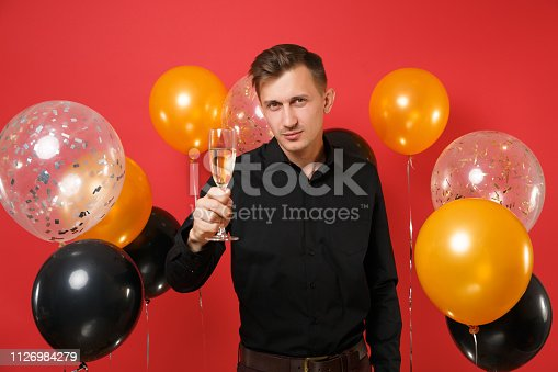 istock Attractive young man in classic shirt pointing hand with glass of champagne on camera on red background air balloons. International Women's Day, Happy New Year, birthday mockup holiday party concept. 1126984279
