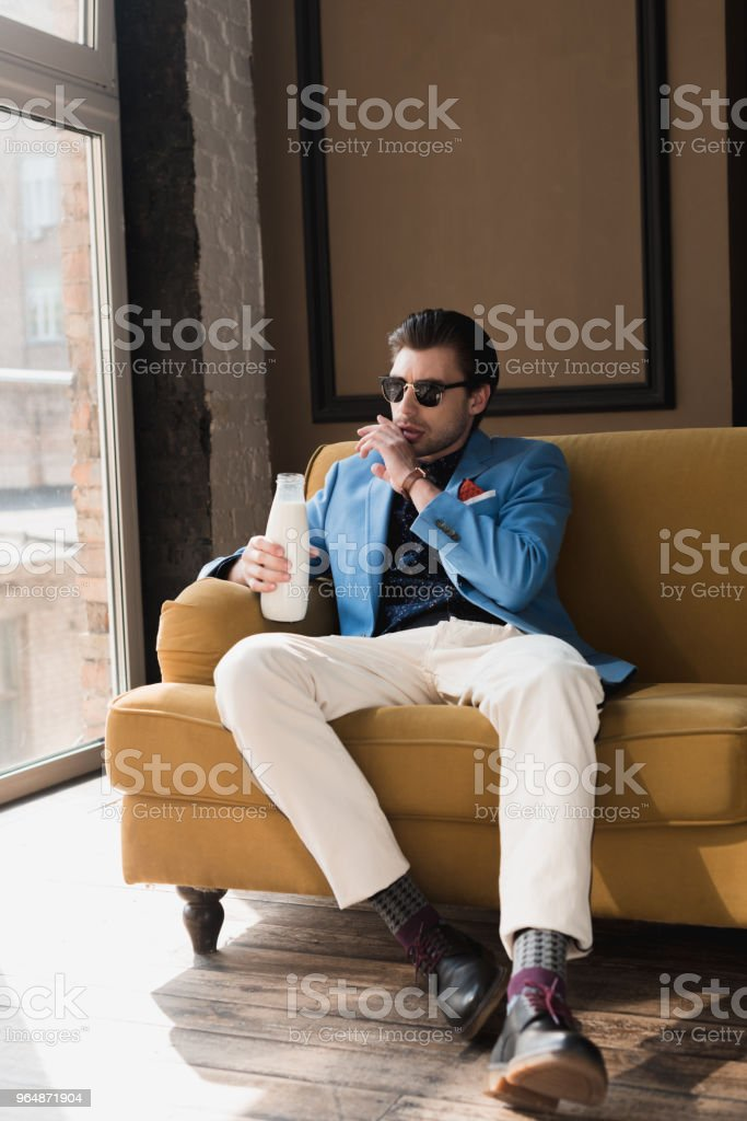 attractive young man in stylish suit sitting on couch with bottle of milk and wiping mouth with hand royalty-free stock photo