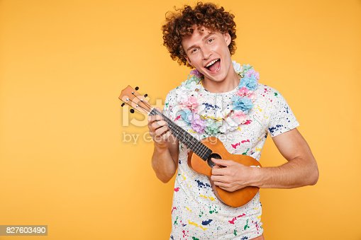 istock Attractive young man in summer clothes playing ukulele 827603490