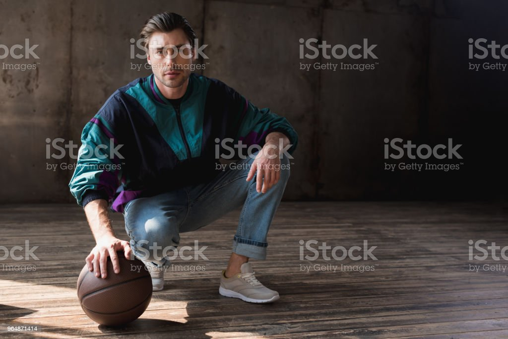 attractive young man in vintage windcheater with basketball ball sitting squats on wooden floor royalty-free stock photo