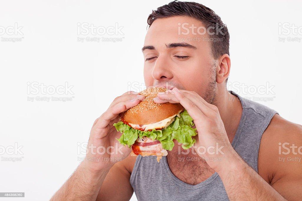 Attractive young man is eating unhealthy hamburger stock photo