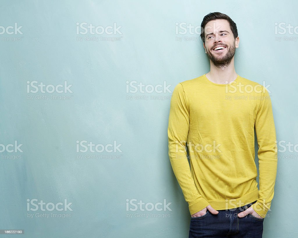 Attractive young man laughing against blue background stock photo