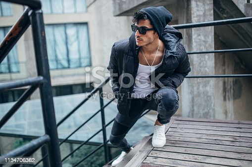 Young, handsome man with black jacket, sunglasses and hat standing on stair.