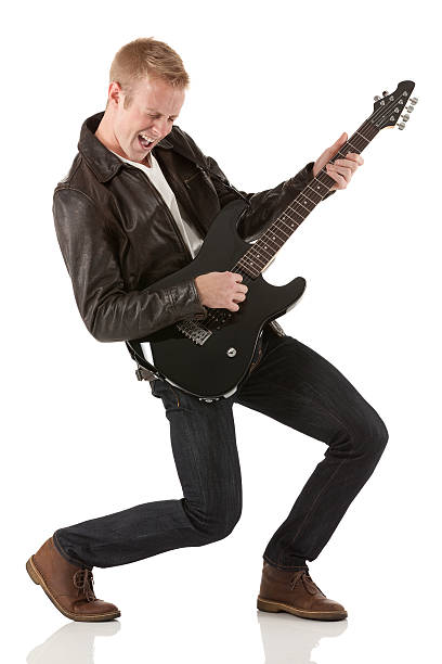 Attractive young man playing a guitar stock photo