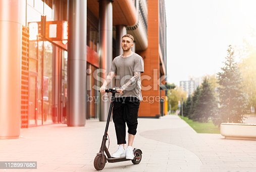 istock Attractive young man riding a kick scooter at cityscape background. 1128997680