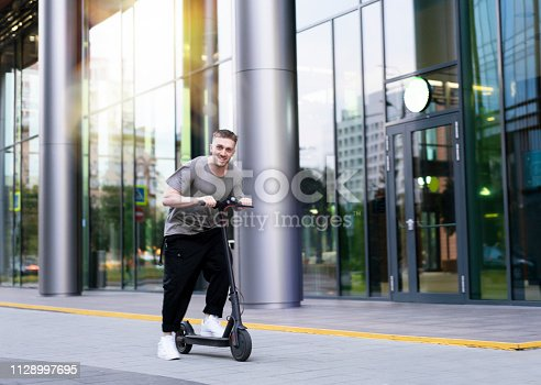 istock Attractive young man riding a kick scooter at cityscape background. 1128997695