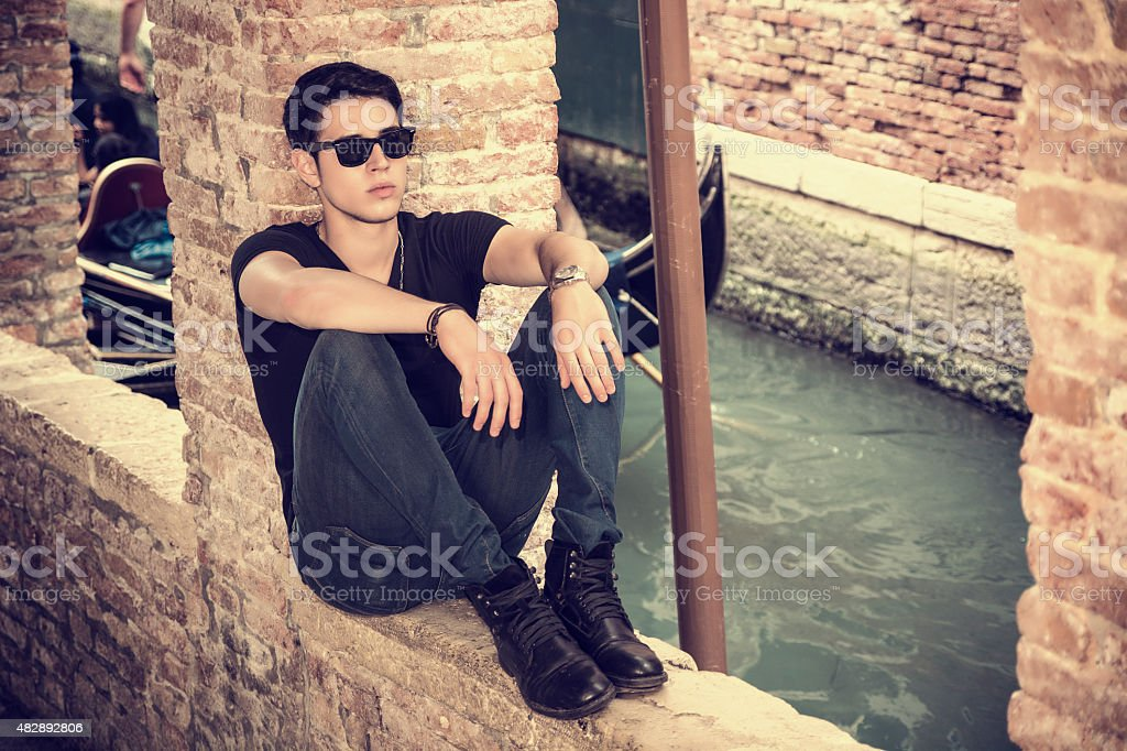 Attractive young man sitting against brick wall stock photo