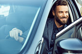 istock Attractive young man sitting in car 629784876