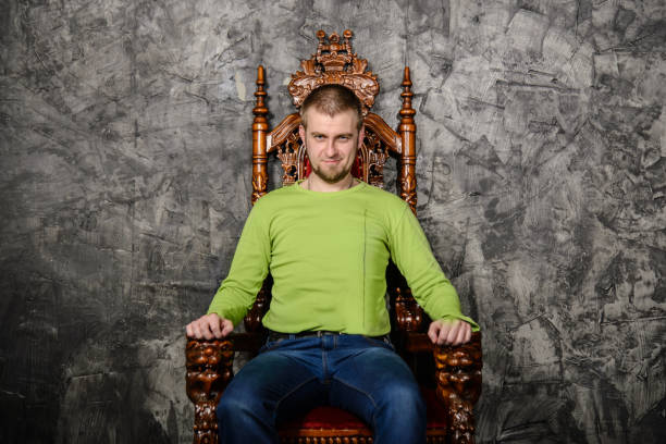 attractive young man sitting on the throne - 王座 ストックフォトと画像