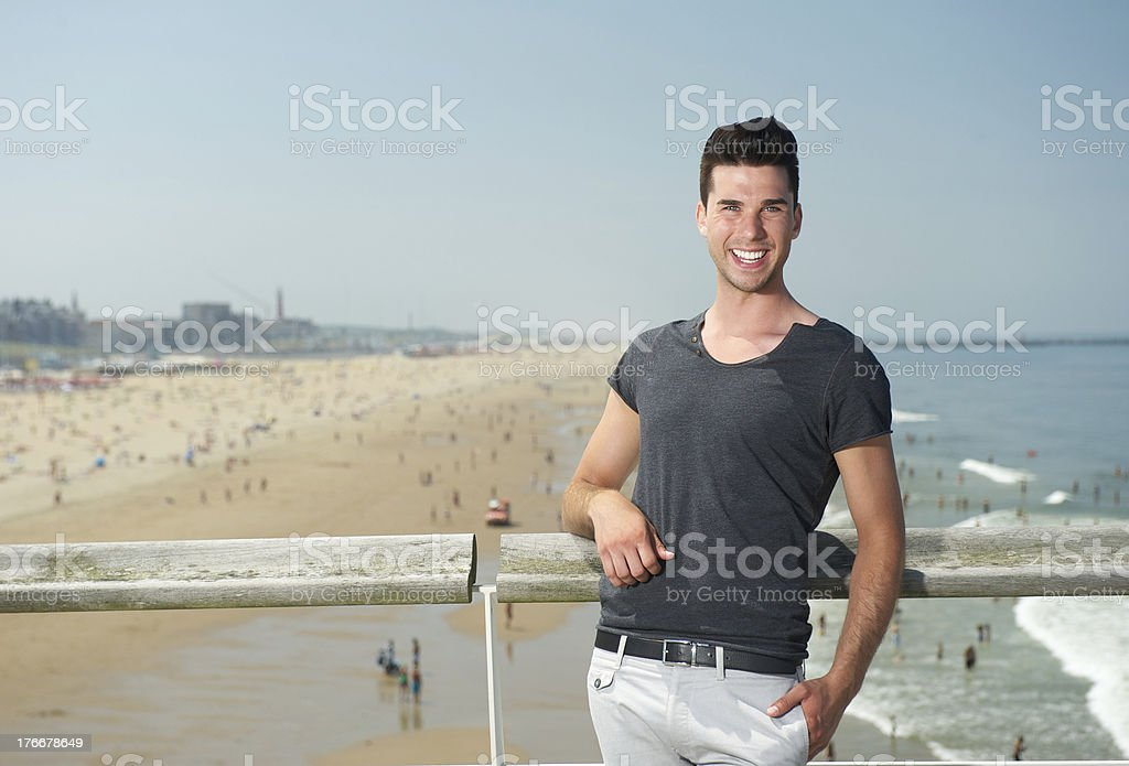 Attractive young man smiling at the beach royalty-free stock photo