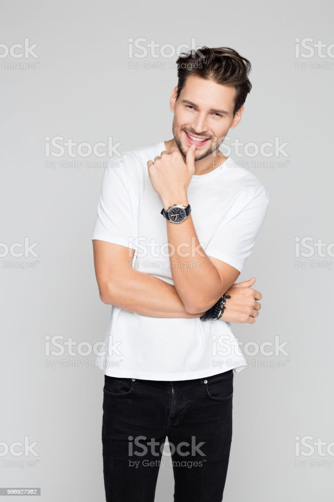 Attractive young man smiling Portrait of attractive young man smiling on grey background 25-29 Years Stock Photo