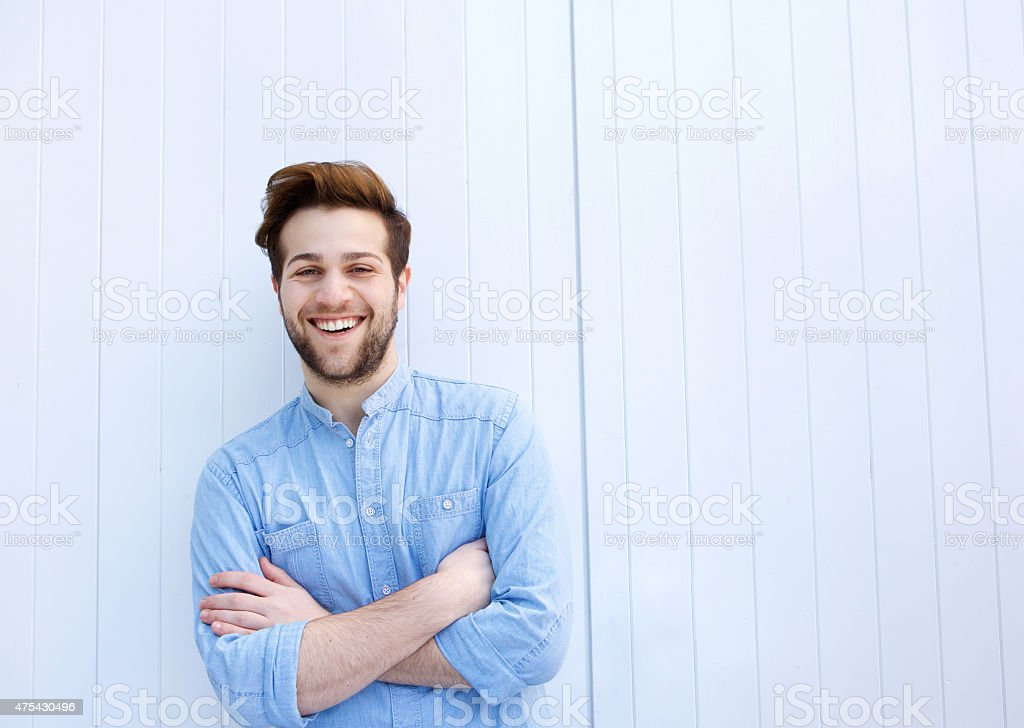 Attractive young man smiling with arms crossed stock photo