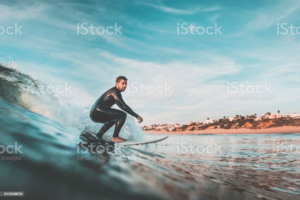 Attractive young man surfing a wave off the coast stock photo