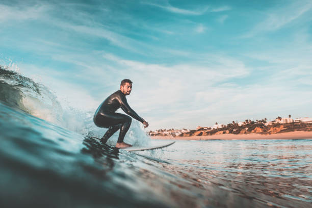 attractive young man surfing a wave off the coast - surf foto e immagini stock